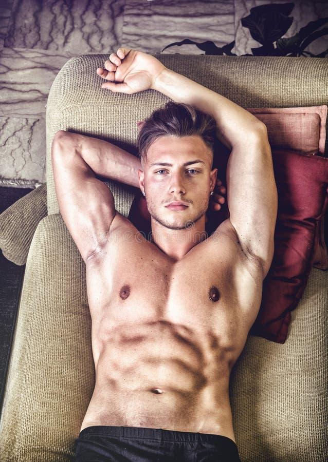 Homem novo em topless no sofá fotos de stock