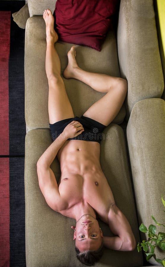Homem novo em topless no sofá foto de stock royalty free