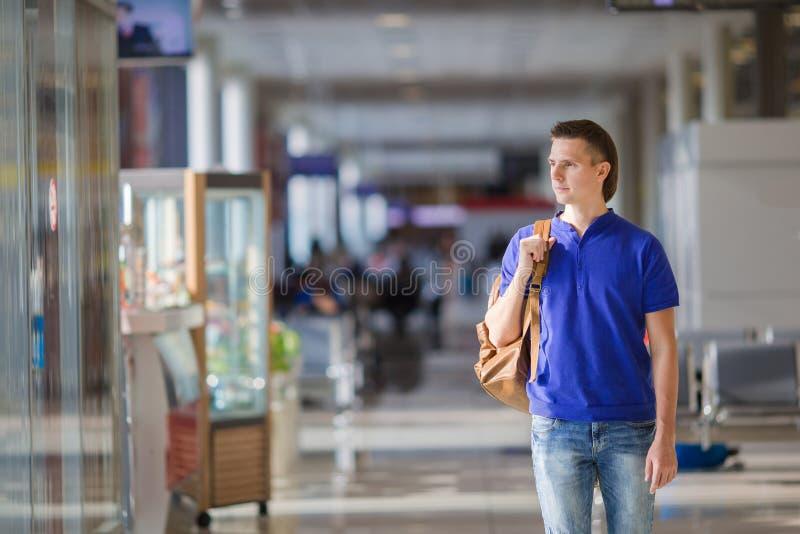 Homem novo em um aeroporto interno imagem de stock