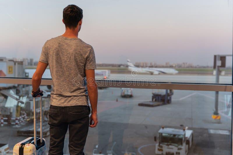 Homem novo em um aeroporto que olha os planos antes da partida imagens de stock