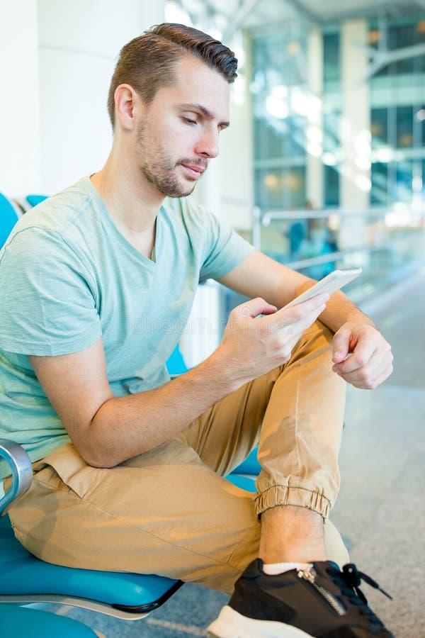Homem novo em um avião de espera do voo da sala de estar do aeroporto Homem caucasiano com o smartphone na sala de espera fotos de stock
