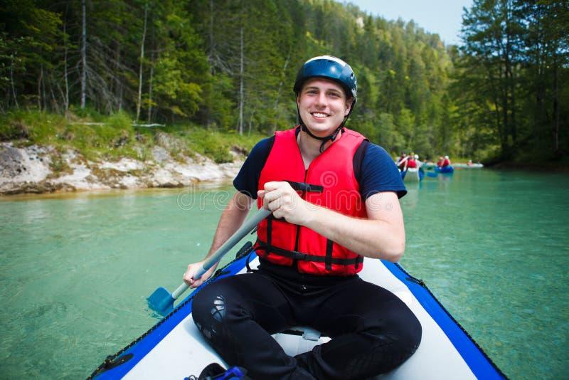 Homem novo em um barco da jangada, remando, smili fotos de stock royalty free