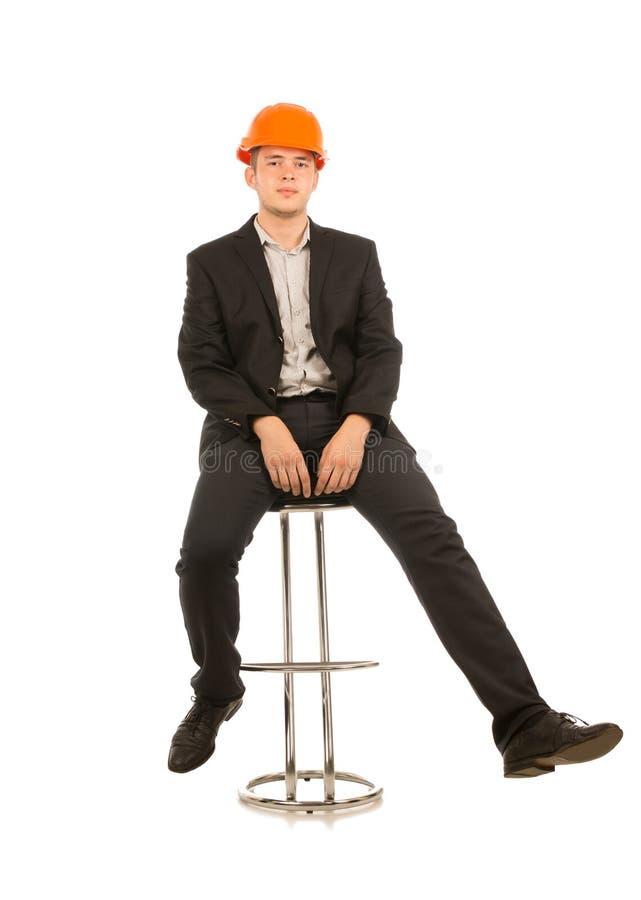 Homem novo em um capacete de segurança que senta-se em um tamborete de barra imagem de stock