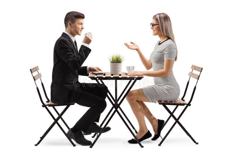 Homem novo em um cofee bebendo e no assento do terno em uma tabela com uma jovem mulher foto de stock