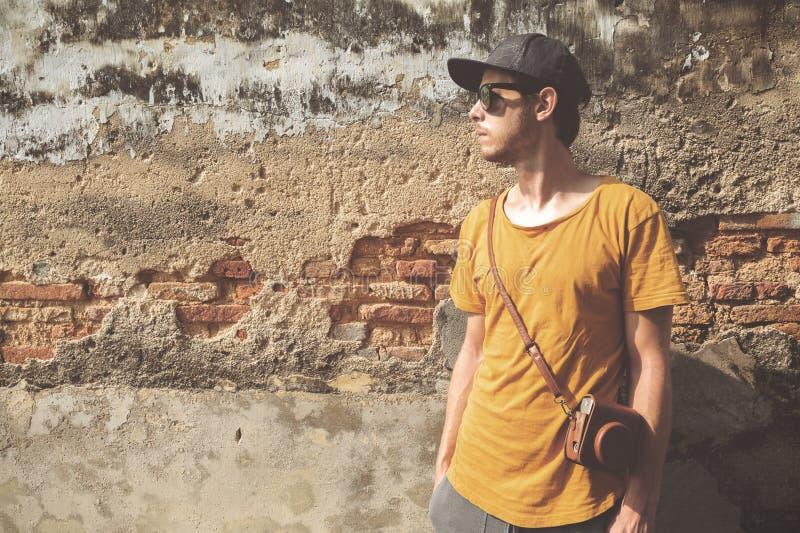 Homem novo em um equipamento do verão que está ocasionalmente na frente de uma parede velha imagem de stock royalty free