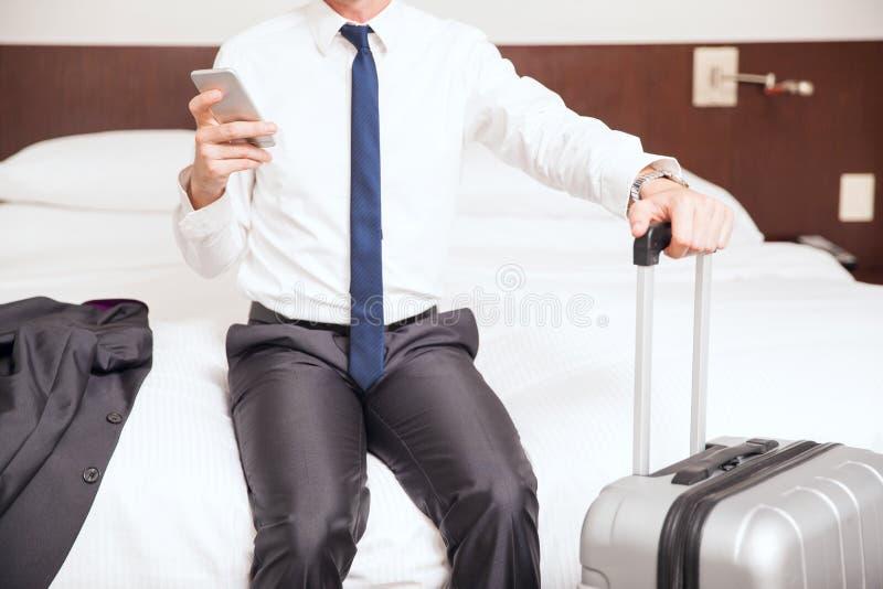 Homem novo em um hotel durante a viagem de negócios imagem de stock