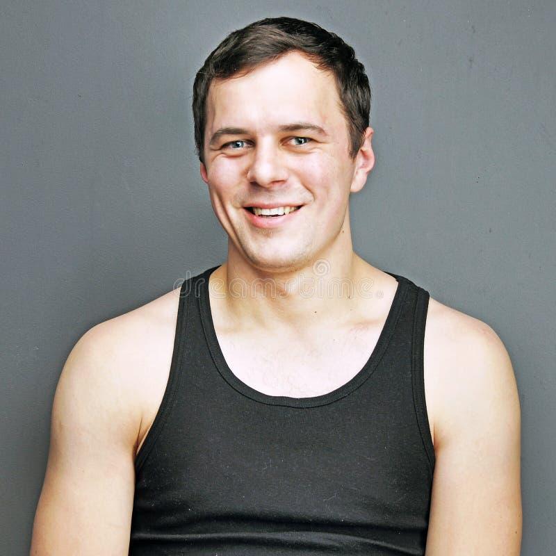 Homem novo em um sorriso preto do t-shirt fotos de stock