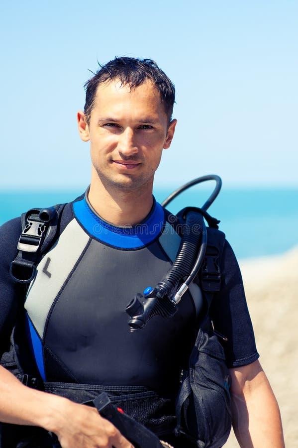 Homem novo em um terno de mergulho imagem de stock royalty free