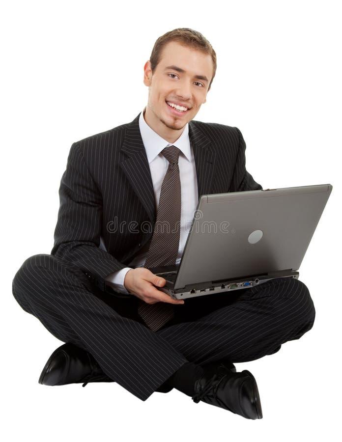Homem novo em um terno de negócio preto com um portátil foto de stock