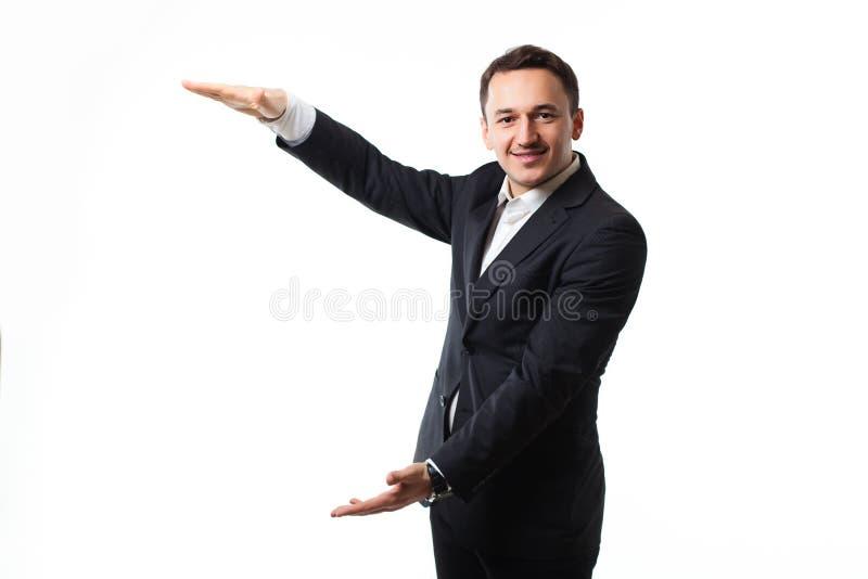 Homem novo em um terno em um fundo branco que mostra sinais imagens de stock royalty free