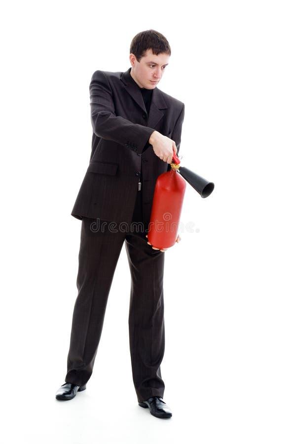 Homem novo em um terno que prende um extintor de incêndio. foto de stock