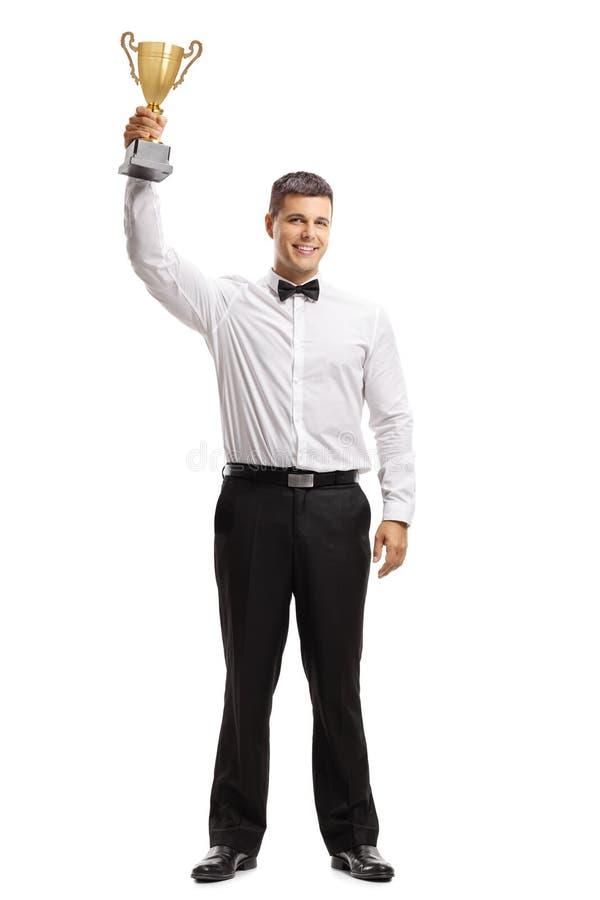 Homem novo em um tux que guarda um troféu dourado imagem de stock royalty free