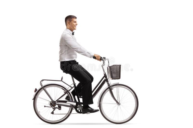 Homem novo em um tux que monta uma bicicleta imagens de stock