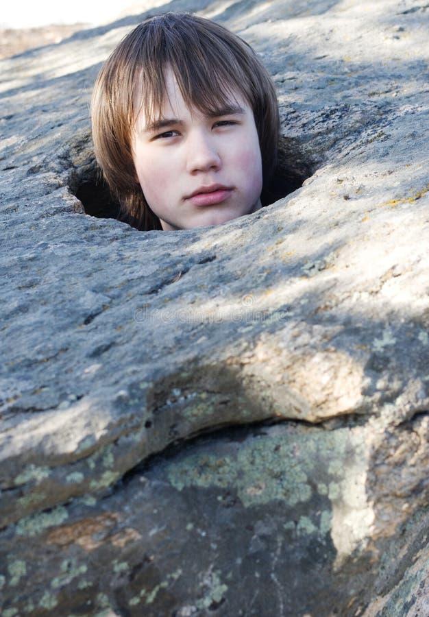 Homem novo em uma abertura na pedra na natureza fotografia de stock
