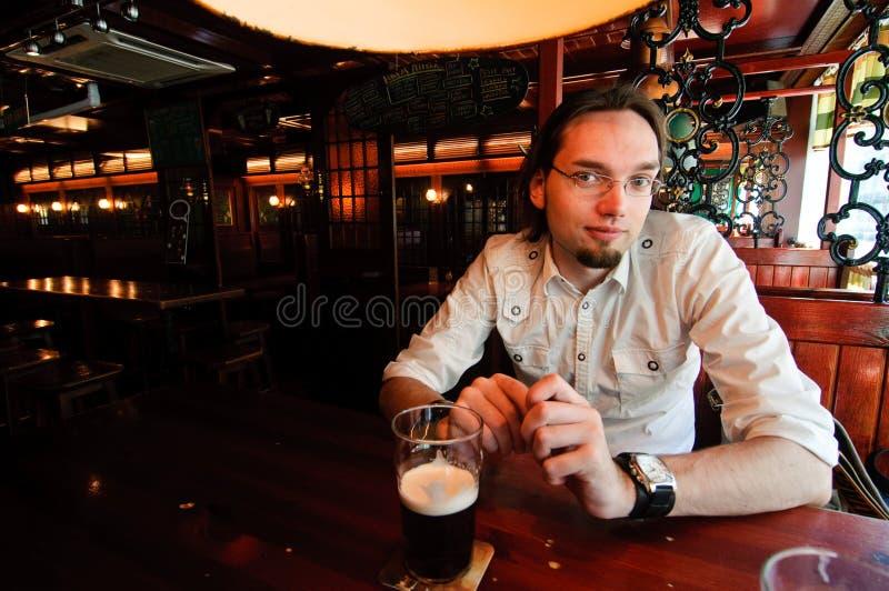 Homem novo em uma barra irlandesa foto de stock