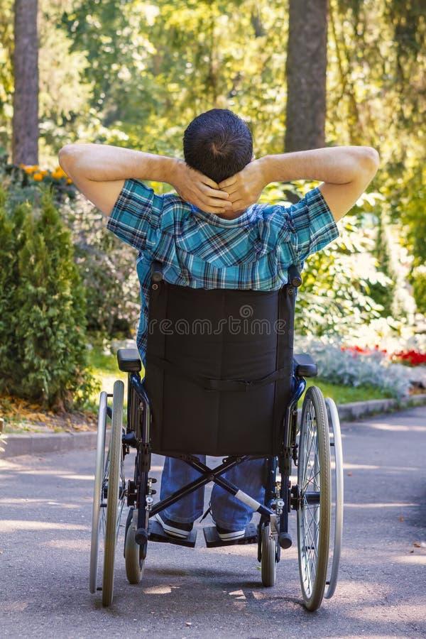 Homem novo em uma cadeira de rodas que aprecia o ar fresco em um dia ensolarado foto de stock royalty free