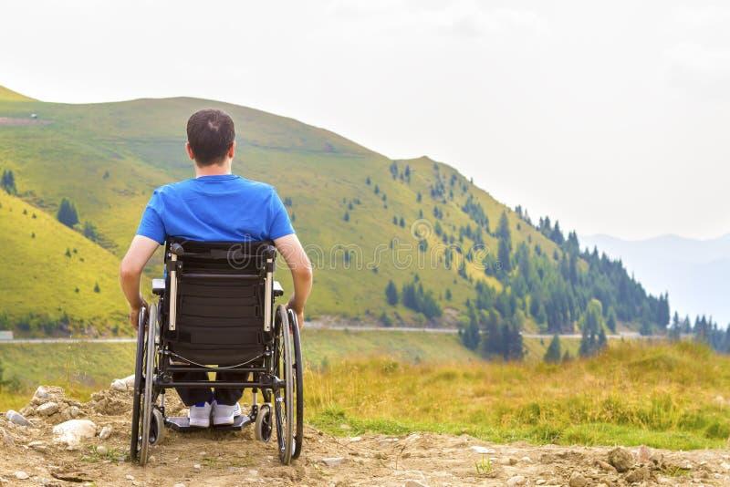 Homem novo em uma cadeira de rodas que aprecia o ar fresco em um dia ensolarado fotos de stock