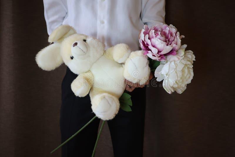 Homem novo em uma camisa branca e em umas calças pretas que guardam uma lebre do brinquedo Um homem com um coelho grande do brinq imagens de stock royalty free