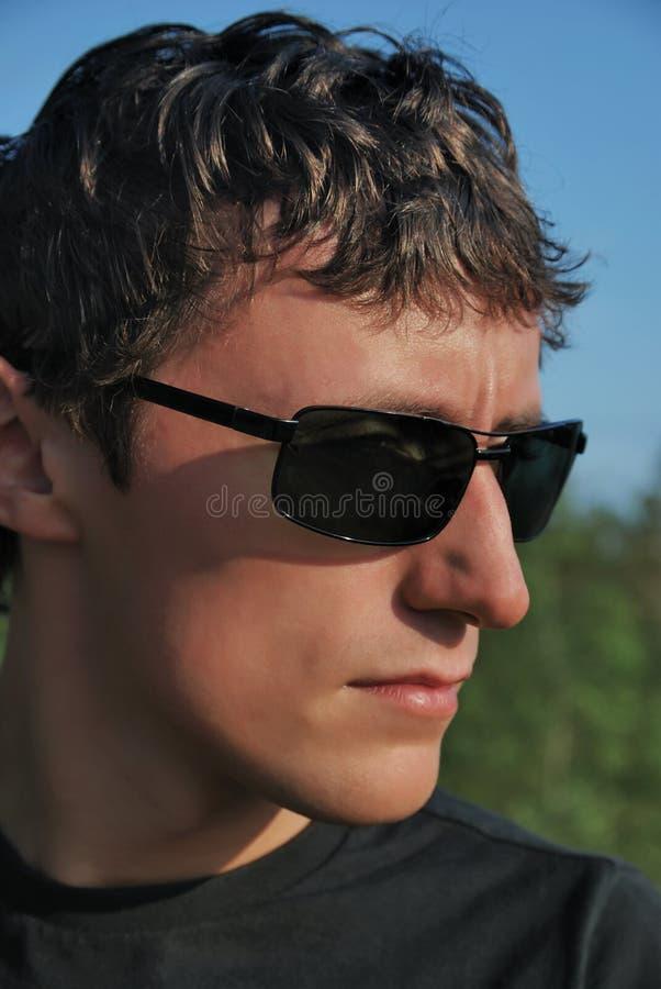 Homem novo em vidros escuros. imagens de stock