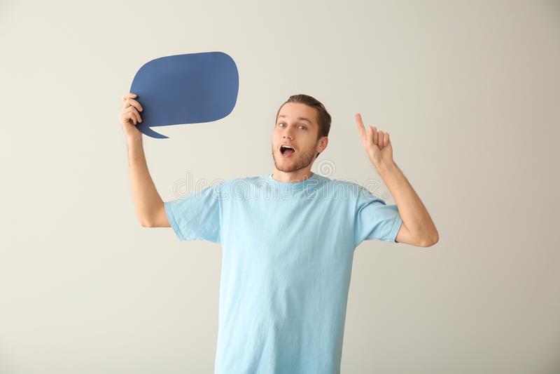 Homem novo emocional com bolha vazia do discurso no fundo claro fotos de stock royalty free