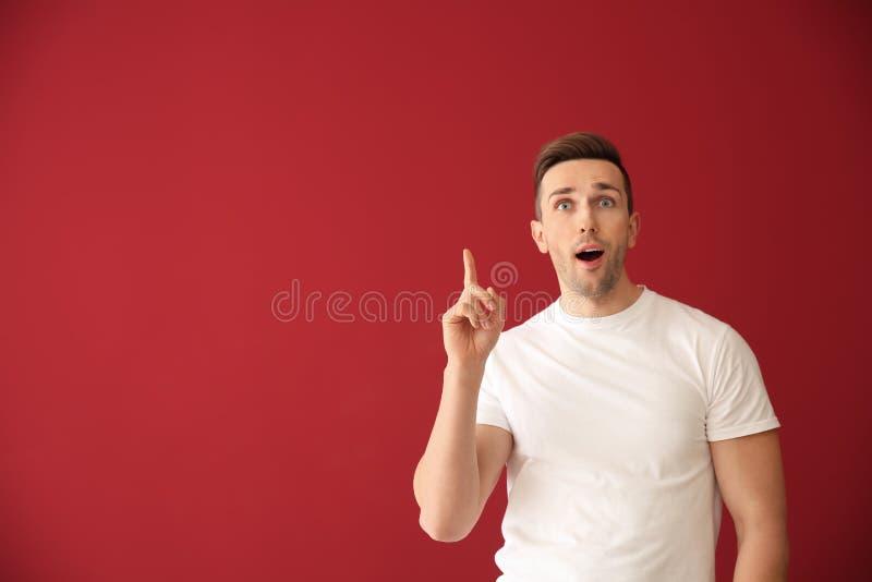 Homem novo emocional com o indicador aumentado no fundo da cor fotografia de stock royalty free