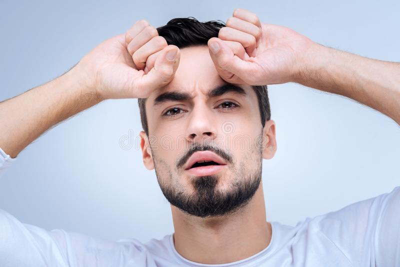 Homem novo emocional que pressiona seus punhos à testa e que olha preocupado imagem de stock