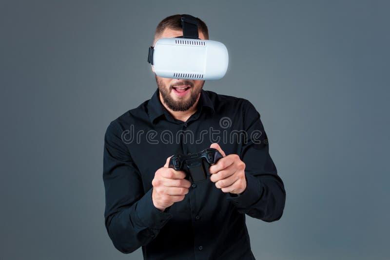 Homem novo emocional que usa uns auriculares de VR e experimentando a realidade virtual no fundo cinzento imagens de stock