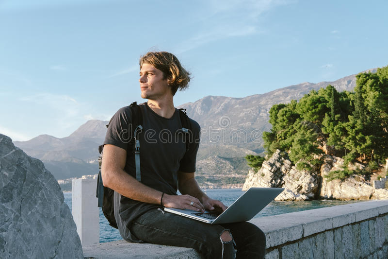 Homem novo encantador que trabalha no portátil perto do mar, wor autônomo imagem de stock royalty free