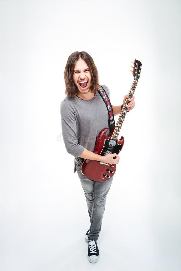 Homem novo engraçado que canta e que joga a guitarra elétrica foto de stock