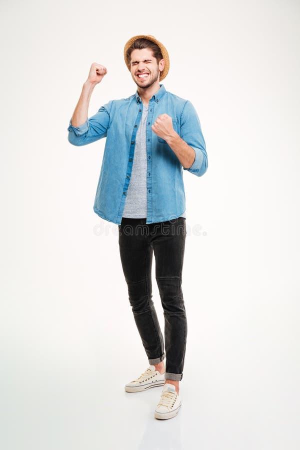 Homem novo entusiasmado feliz que está e que comemora o sucesso imagens de stock royalty free