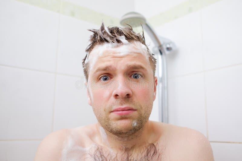 Homem novo espumado caucasiano preocupado depois que a água no chuveiro foi desligada, olhando a câmera imagem de stock