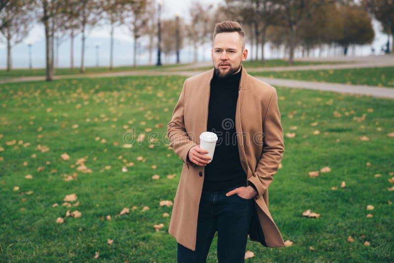 Homem novo farpado considerável nos óculos de sol que bebe o café no parque, espaço da cópia no copo fotos de stock royalty free