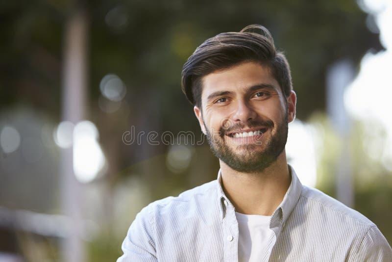 Homem novo farpado de sorriso que senta-se fora, retrato fotografia de stock royalty free