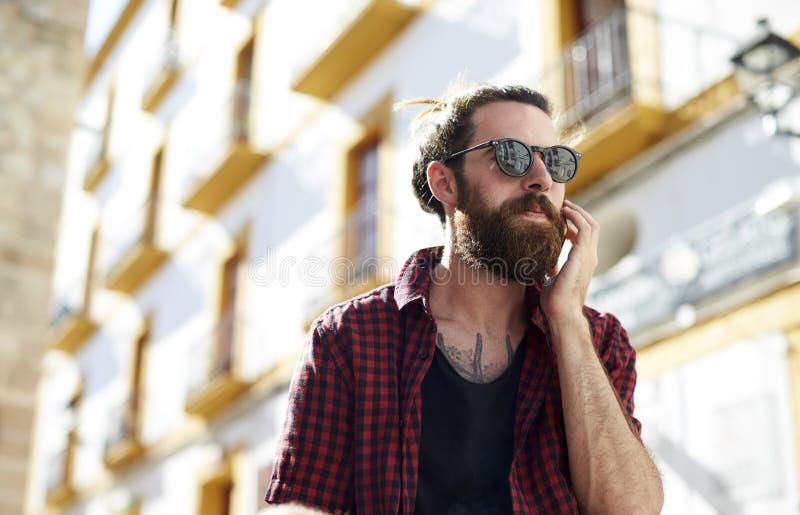 Homem novo farpado nos óculos de sol usando o telefone, Ibiza, Espanha fotografia de stock royalty free