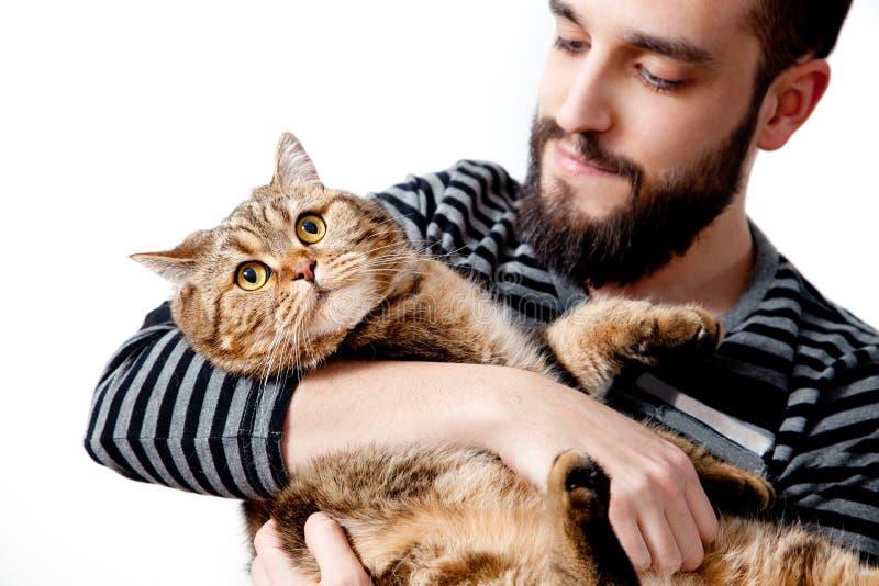 homem novo farpado que abraça seu gato bonito no fundo branco imagem de stock