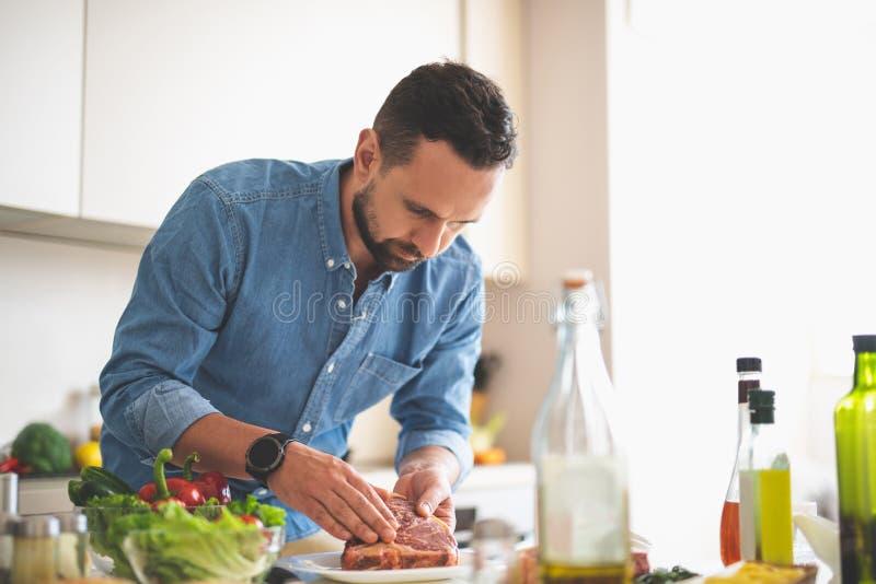 Homem novo farpado que cozinha a carne ao estar perto da mesa de cozinha foto de stock royalty free