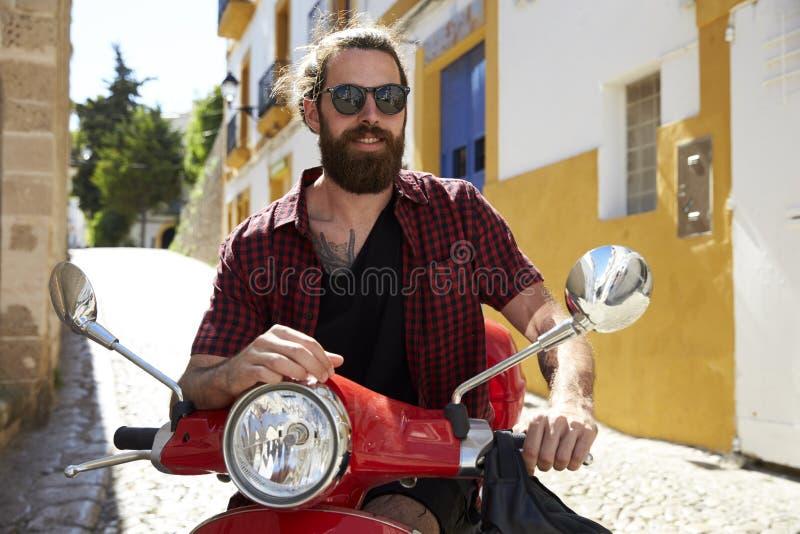 Homem novo farpado que senta-se no 'trotinette' de motor, Ibiza, Espanha fotografia de stock
