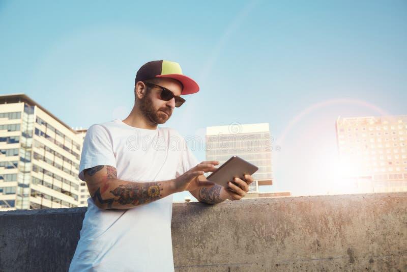 Homem novo farpado Tattooed com uma tabuleta na cidade imagens de stock royalty free