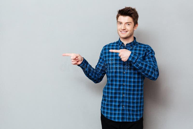 Homem novo feliz atrativo que está sobre a parede cinzenta e apontar imagem de stock royalty free