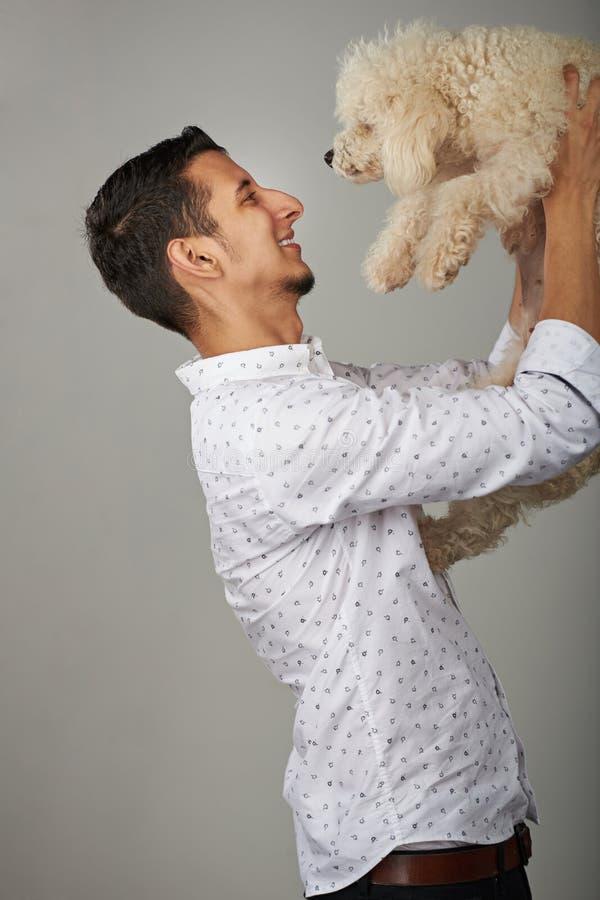 Homem novo feliz com cão fotografia de stock royalty free