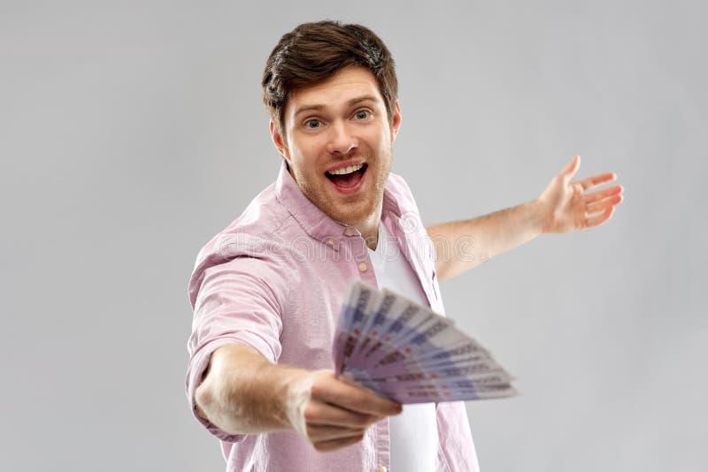 Homem novo feliz com o fã do euro- dinheiro imagem de stock