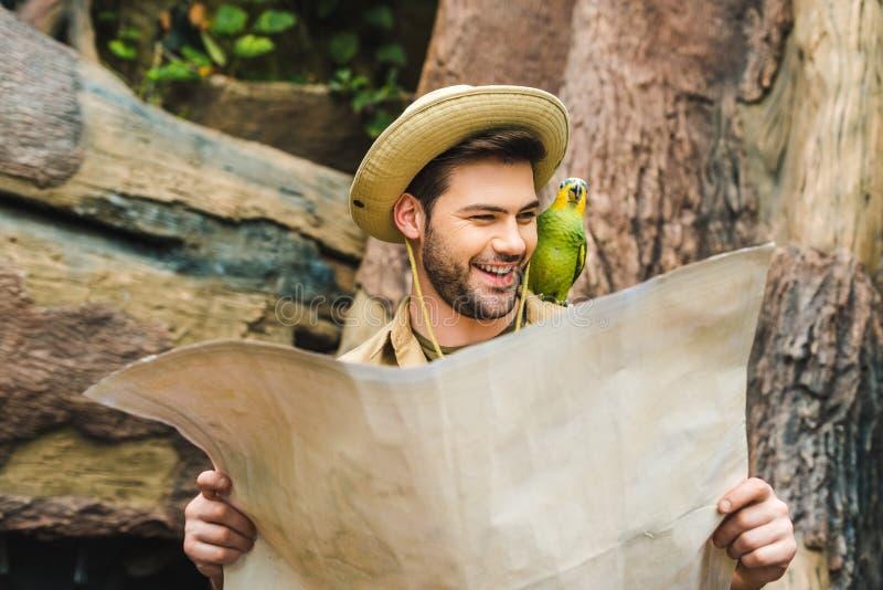 homem novo feliz com o papagaio no ombro e no mapa fotos de stock royalty free