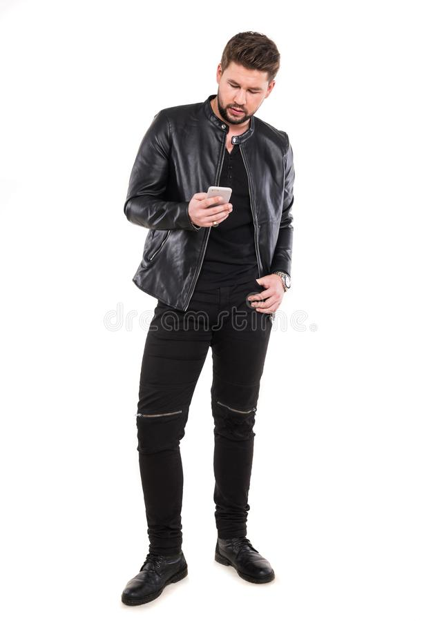 Homem novo feliz com o telefone celular que levanta no estúdio imagem de stock royalty free