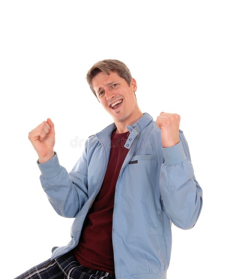 Homem novo feliz com punhos acima fotos de stock royalty free
