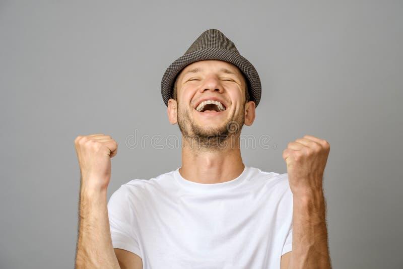 Homem novo feliz com seus braços acima no gesto da vitória fotografia de stock