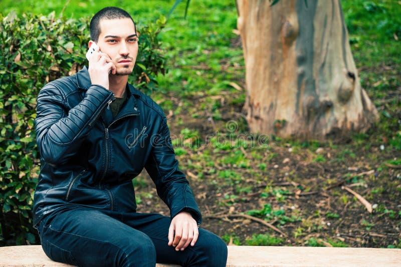 Homem novo feliz com smartphone Fala no telefone imagem de stock royalty free