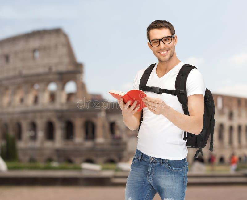 Homem novo feliz com viagem da trouxa e do livro foto de stock royalty free