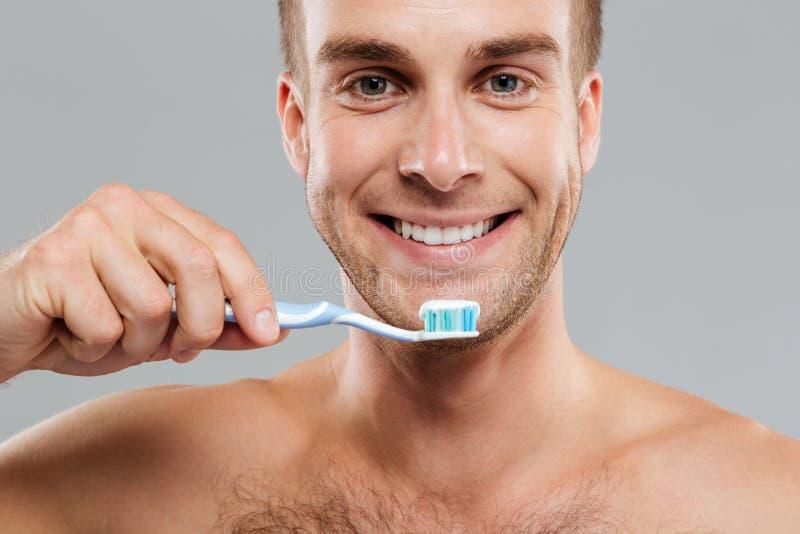 Homem novo feliz do close up que guarda a escova de dentes com dentífrico imagem de stock