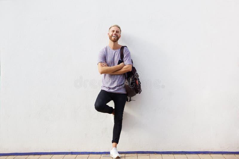 Homem novo feliz do corpo completo com a barba que inclina-se contra a parede com os braços cruzados imagem de stock royalty free