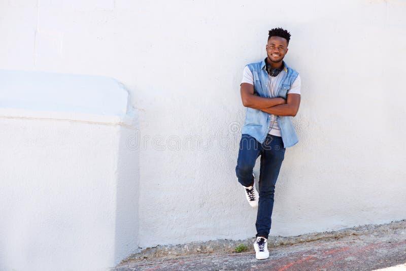 Homem novo feliz do corpo completo que inclina-se contra a parede com fones de ouvido fotos de stock